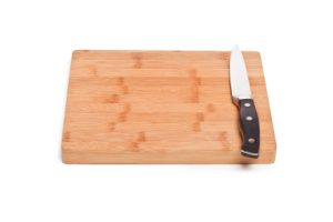 Isolated image of wooden cutting board and knife lying on a white background